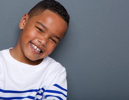Close-up portret van een knappe kleine jongen lachend op een grijze achtergrond