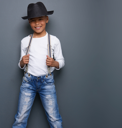 cool kids: Portrait of a little boy smiling with black hat and suspenders on gray background Stock Photo