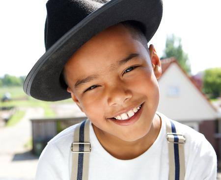 屋外の帽子と笑顔かわいい男の子の肖像画を間近します。