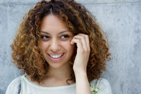 mixed race woman: Close up portrait of a smiling young african american woman with hand in hair