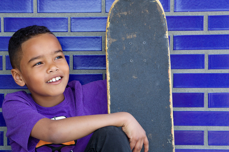 Close up portrait of a cute kid smiling outdoors with skateboard photo