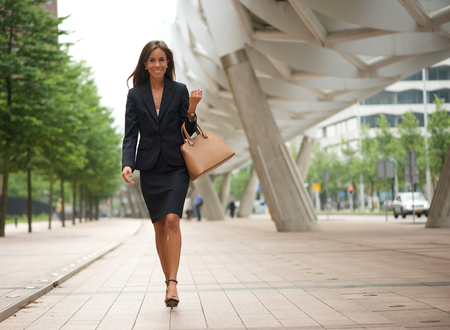 skirt suit: Portrait of a business woman walking in the city with handbag