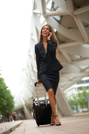 sidewalk talk: Portrait of a business woman traveling and talking on mobile phone outdoors