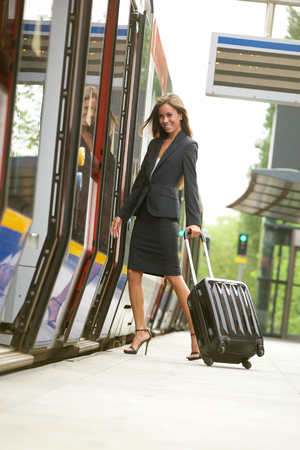 Business woman traveling with suitcase by train photo