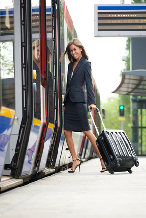 Young business woman embarking on train with suitcase photo