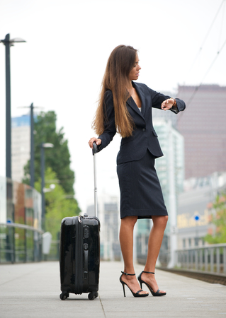 Portrait of a business woman checking time at train station photo