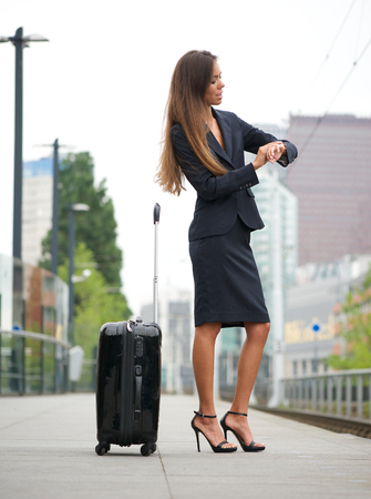 Portrait of a business woman traveling by train and checking time photo