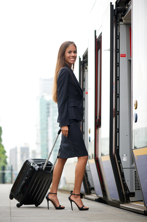 embark: Young business woman entering train with suitcaise