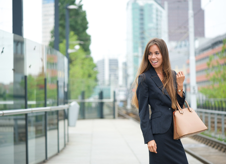 Portrait of a business woman smiling at outdoor train station in the city photo