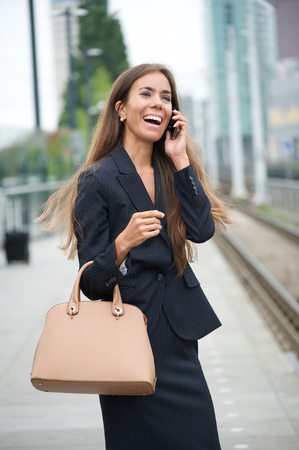 Portrait of a businesswoman calling by phone at train station Imagens