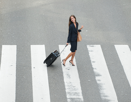 Portrait of a businesswoman crossing street at crossway with travel bags photo