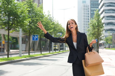 Portrait of a businesswoman with raised arm calling for taxing photo