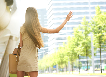 behind: Young woman from behind with raised arm waving for taxi in the city Stock Photo