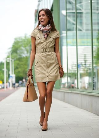 Portret van een modieuze jonge vrouw lopen in de stad met zak