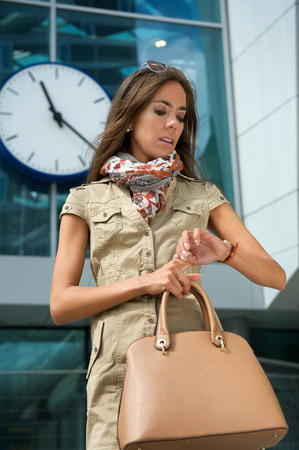 Portrait of a fashionable young woman looking at watch outdoors photo