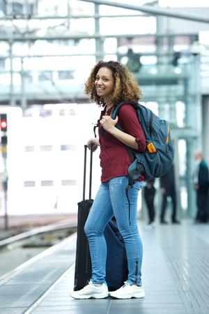mujer con maleta: Mujer joven que sonríe en la plataforma de la estación de tren con maletas Foto de archivo