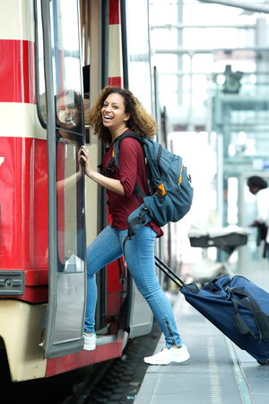Smiling young woman entering train with bags photo