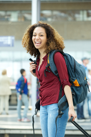 Portrait of a cheerful young woman smiling with luggage at airport photo