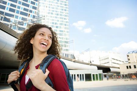 Portrait of a young woman smiling with backpack in the city photo