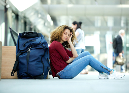 sleeping bag: Tired young woman sleeping at airport with luggage