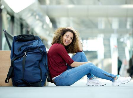 Portrét mladé ženy usmívající se s taškou na nádraží