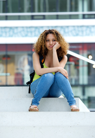 Portrait of a female student sitting outside with grumpy expression on face photo