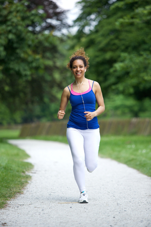 american music: Young woman running on footpath in the park