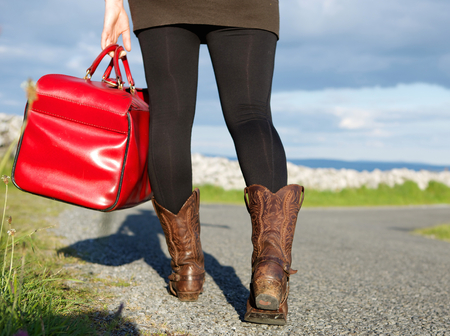 woman holding bag: Woman holding bag and walking on road int he countryside