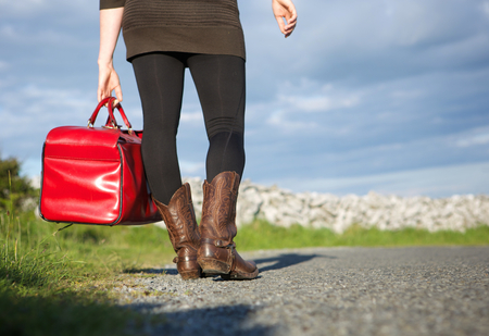Woman traveler holding red bag outdoors photo