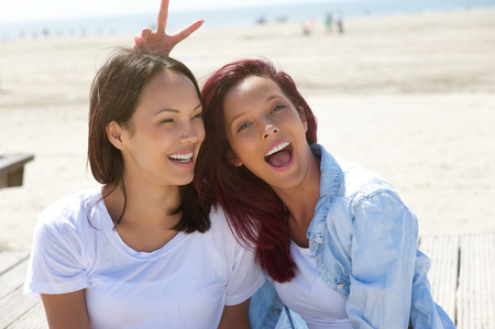 Close up portrait of cheerful sisters having fun at the beach photo