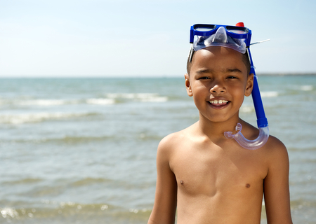 Close Up Portrait Of A Little Boy Smiling With Snorkel At The Beach
