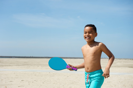 Portrait of a smiling little boy playing paddle ball at the beach photo