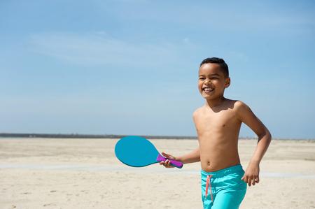 niño sin camisa: Retrato de un niño sonriente jugando a la pelota paleta en la playa