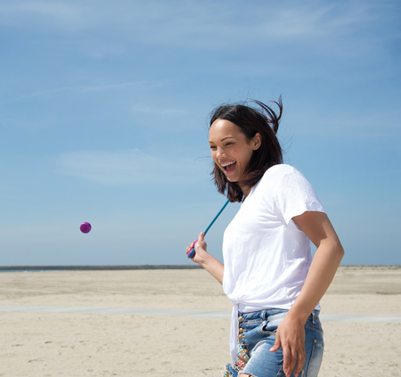 Portrait of a happy young woman playing tennis at the beach photo
