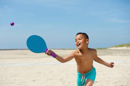niño sin camisa: Retrato de un niño activo jugando en la playa
