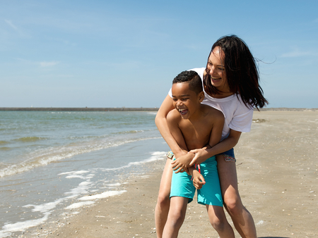 Portrait of a smiling mother and son playing at the beach  Stock Photo