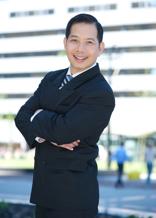 asian businessman: Portrait of a businessman standing outdoors with arms crossed Stock Photo