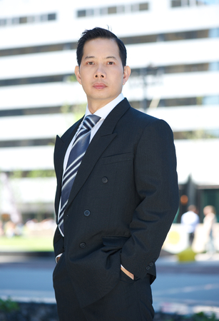 serious businessman: Formal portrait of an asian businessman standing outside  Stock Photo