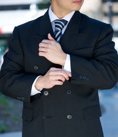 cuff: Close up portrait of a businessman adjusting cuff  Stock Photo