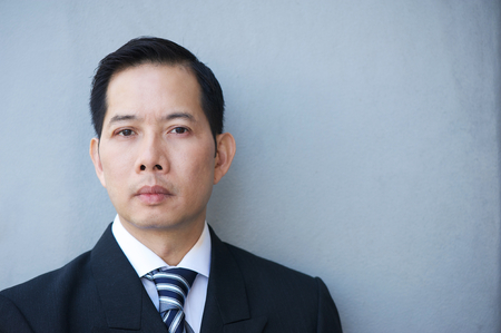 chinese businessman: Close up portrait of a serious businessman against gray background