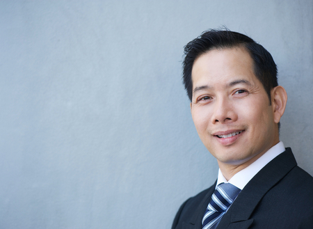 chinese face: Close up portrait of a friendly businessman smiling on gray background