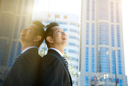 look in mirror: Close up portrait of a smiling businessman looking up at buildings in the city Stock Photo