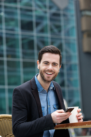 cute guy: Portrait of a cute guy smiling with mobile phone