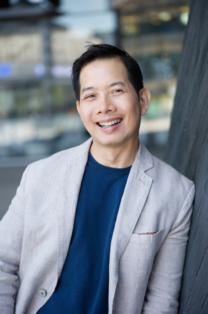 Portrait of a cool middle aged asian man smiling outdoors Stock Photo