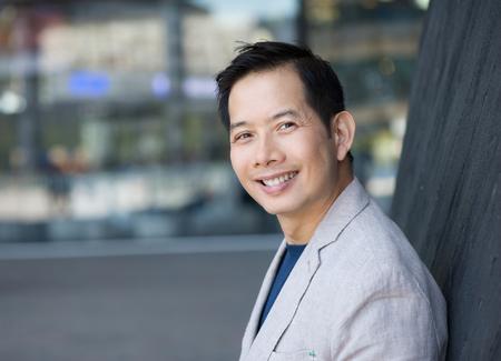 Close-up portret van een trendy Aziatische man die lacht buitenshuis