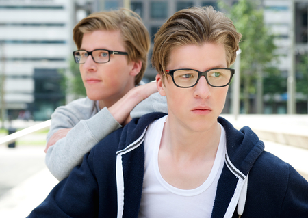 Close up portrait of male twin fashion models with glasses posing outdoors photo