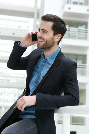 cute guy: Portrait of a cute guy calling by mobile phone indoors