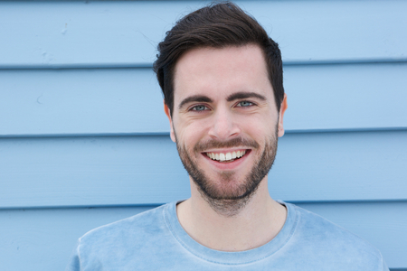 brown hair: Close up portrait of a handsome young man with beard smiling on blue background Stock Photo