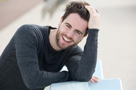 Close-up portret van een knappe man glimlachend met de hand in het haar