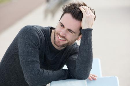 Close-up portret van een aantrekkelijke man glimlachend met de hand in het haar